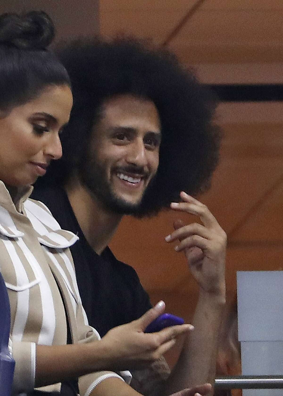 Colin Kaepernick watches Serena Williams play Venus Williams during the third round of the U.S. Open tennis tournament Friday, Aug. 31, 2018, in New York. (AP Photo/Adam Hunger)