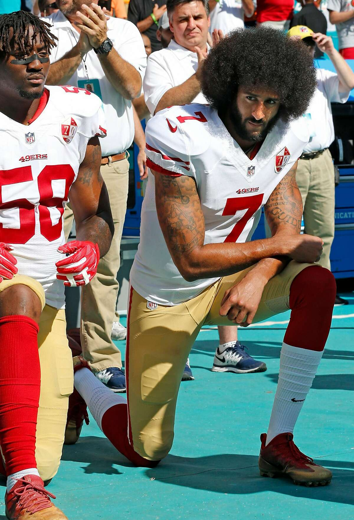 San Francisco 49ers outside linebacker Eli Harold (58) and quarterback Colin Kaepernick (7) take a knee during the national anthem before a game against the Miami Dolphins on Sunday, Nov. 27, 2016 at Hard Rock Stadium in Miami Gardens, Fla. (Al Diaz/Miami Herald/TNS)