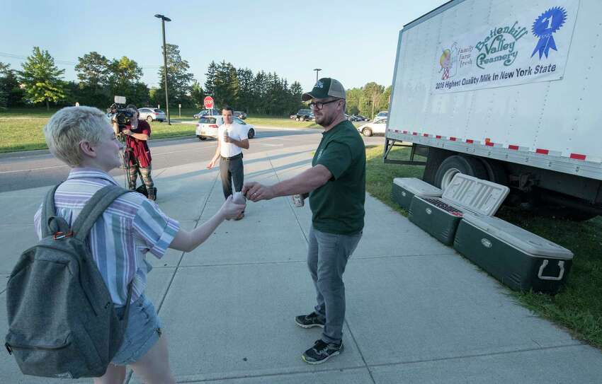 Seth McEachron of the Battenkill Creamery hands out milk to students for them to try at the Niskayuna High School on opening day Sept. 5, 2018 in Niskayuna, N.Y. According to information from the school district the Battenkill Creamery is partnering with the Niskayuna High School, will be selling both chocolate milk and mocha milk in the cafeterias. (Skip Dickstein/Times Union)