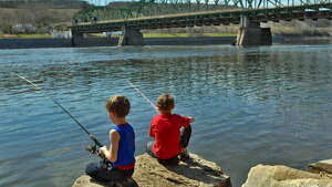 Austin Palmo, 6, left, and his brother Dean Palmo, 8, both of Scotia, fish on the Mohawk River at the Erie Canal Lock 8, in Maalwyck Park in Glenville, NY Wednesday April 15, 2009. (Philip Kamrass / Times Union)