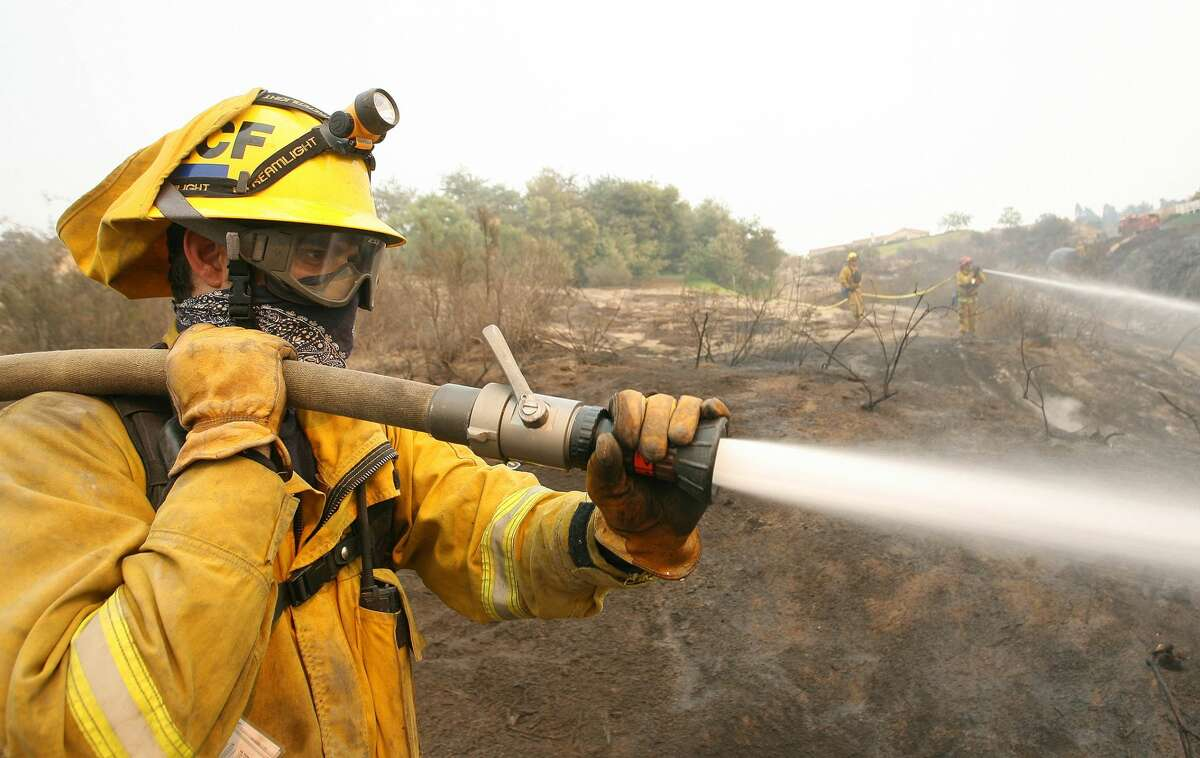 Jason Bracci, a firefighter with the North County Fire Department in Fallbrook, California, cools down a burn area in Fallbrook during the Southern California wildfires of 2007.Bracci was on the initial response team when the fires began, and worked 48 hours straight in battling fires. Now he is on a 24 on, 24 off shift. The entire city's population was evacuated due to the fires.
