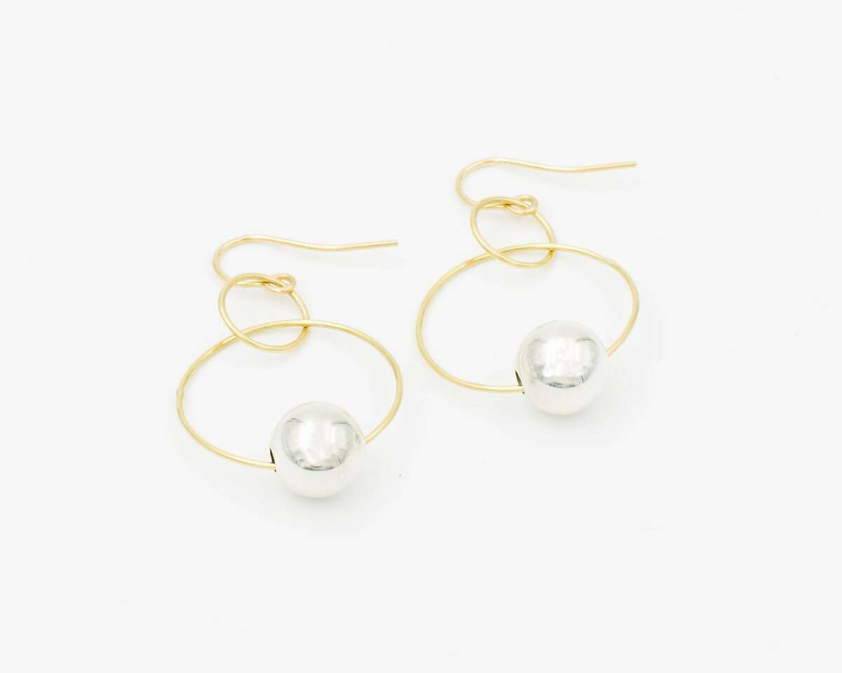 Featuring two interlocking 18k recycled gold hoops with a spherical silver bead, these Blunk double-hoop earrings ($400)�are rooted in a design by the late artist J.B. Blunk. Today, they are crafted by hand in Montana by Clare Clum for Permanent Collection, which also produces them with a bone bead.