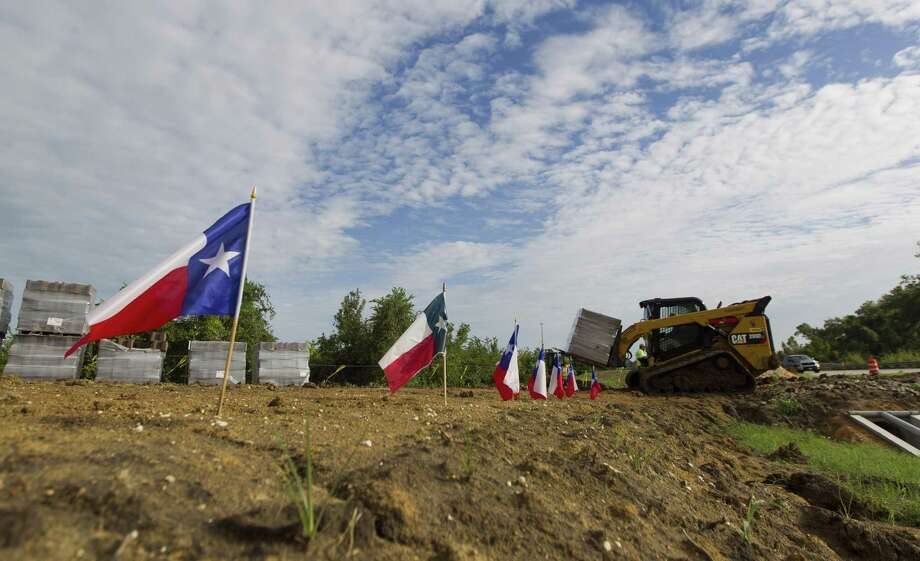 A construction worker moves supplies for Spirit of Texas Bank's 16th location at Texas 105 and Lone Star Parkway on Wednesday, Sept. 5, 2018, in Montgomery. Photo: Jason Fochtman, Houston Chronicle / Staff Photographer / © 2018 Houston Chronicle