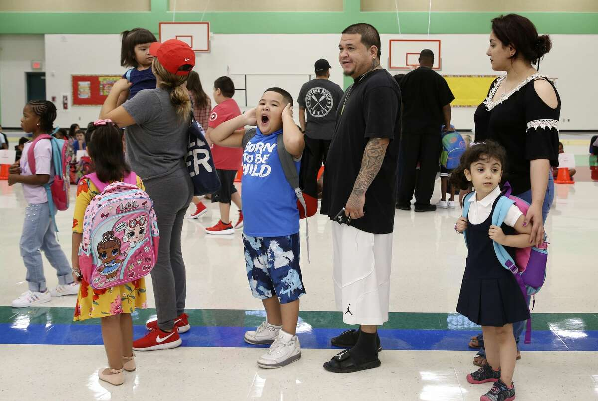 With a big yawn, Sylas Miranda, 7, waits with his father, Jay Miranda, center, and other parents and children in the cafeteria on the first day of classes at the new Dr. Linda Mora Elementary School, Monday, August 27, 2018. The school is named for retired Northside Independent School District Deputy Superintendent for Curriculum and Instruction Dr. Linda Mora.
