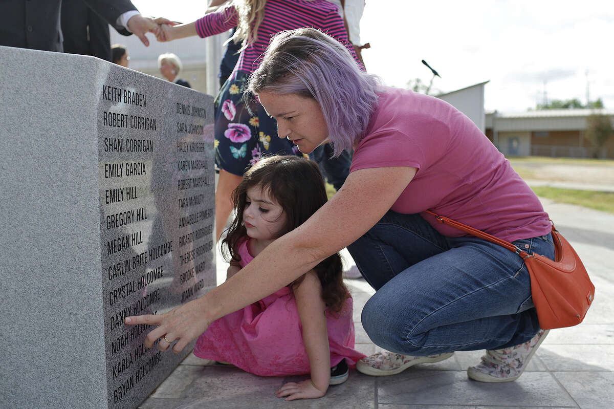 Sarah Slavin points at the name of her brother, Danny Holcombe, as she shows her daughter, Elene Slavin, 3, the nine members of their family listed on the memorial dedicated to the victims from First Baptist Church of Sutherland Springs at the Wilson County District Court Justice Center in Floresville on August 31, 2018.
