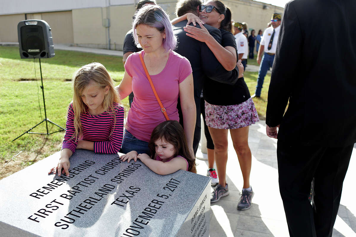 Evelyn Hill, 8, with her aunt, Sarah Slavin, and Sarah's daughter, Elene Slavin, 3, all members of the Holcombe family, look at the memorial dedicated to the victims from First Baptist Church of Sutherland Springs, including nine members of their family, at the Wilson County District Court Justice Center in Floresville on August 31, 2018.