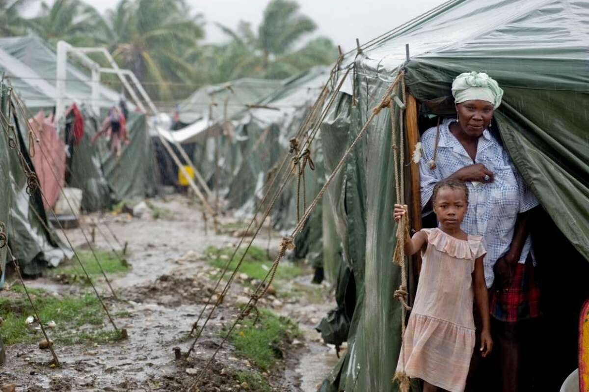 7-year-old Loudmillard Ostal, stands in front of their tent in the Pinchinat IDP Camp with her mother Guerline Telisme., She has 4 other children as well. The Pinchinat IDP Camp is loacted in the town of Jacmel and houses over 5,000 people, a total of 833 families. Save the Children provides WASH activiites as well as Child Friendly programs to the camp.