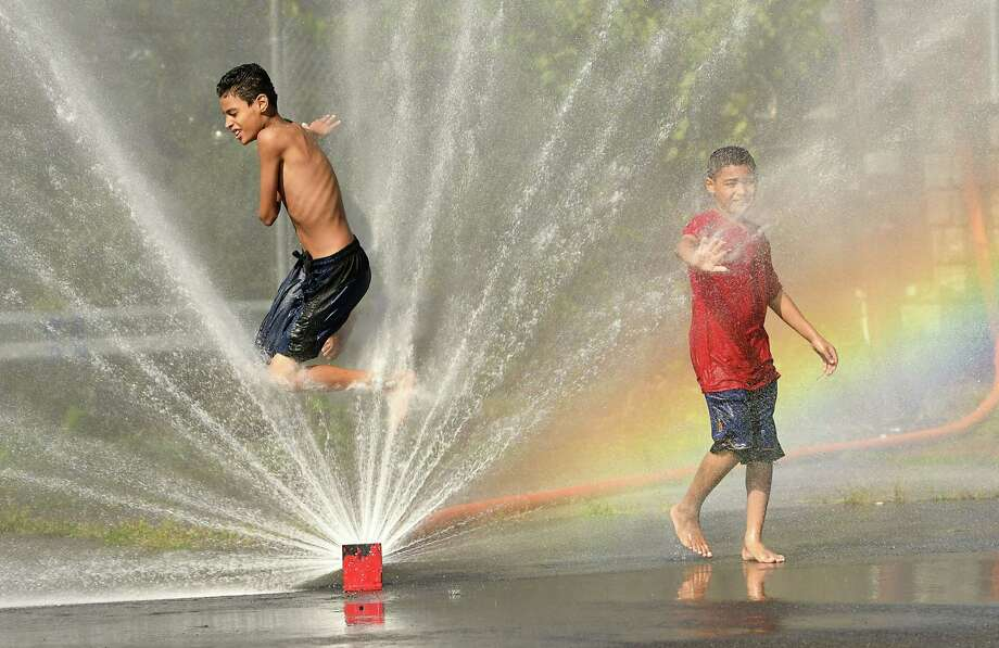 Jacob Garcia, 13, of Troy, left, and Romeo Rivera, 10, stay cool in the spray of a hose at a cooling station at the Little Italy Market Place on Liberty St. on Wednesday, Sept. 5, 2018 in Troy, N.Y. Temperatures hit the 90's today. (Lori Van Buren/Times Union) Photo: Lori Van Buren, Albany Times Union / 20044745A