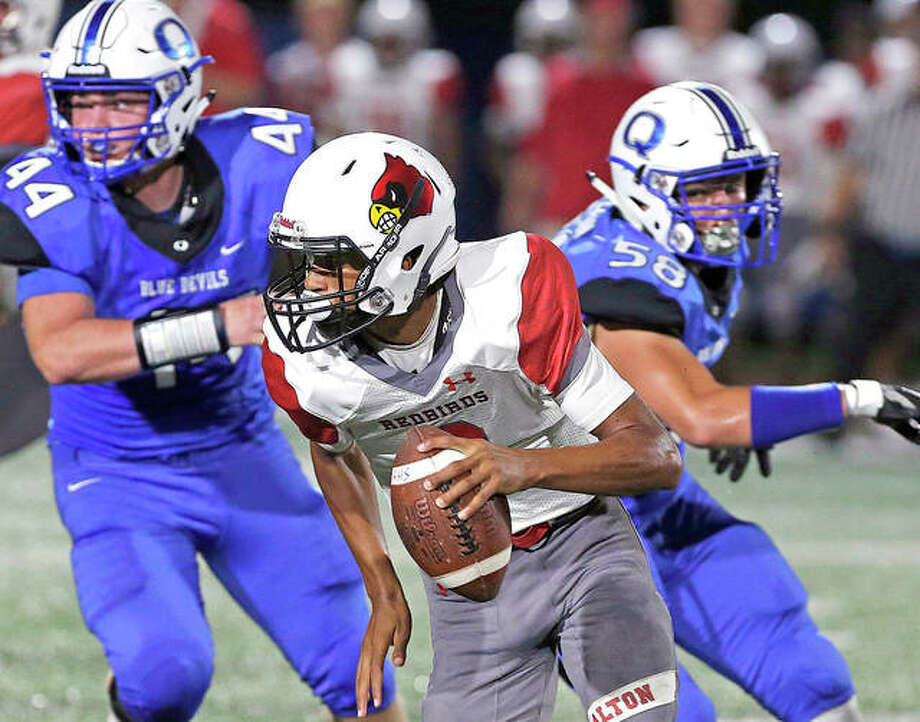 Alton quarterback Andrew Jones scrambles under press from Quincy High's Parker Stegeman Friday night at Quincy's Flinn Stadium. Photo: Jake Shane, Quincy Herald-Whig | For The Telegraph