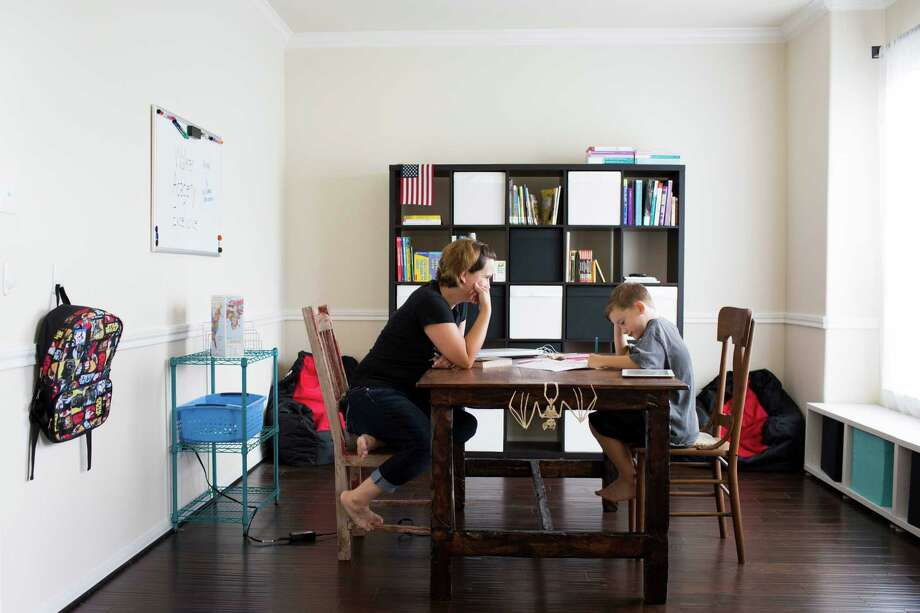 Heidi Walker sits across from her son Roanin Walker, 7, while he studies at his home classroom in Kingwood, Thursday, Aug. 25, 2016. Heidi and her husband decided to homeschool Roanin this academic year after he was denied special education. Roanin has been diagnosed with attention deficit disorder, anxiety and sensory processing disorder. ( Marie D. De Jesus / Houston Chronicle ) Photo: Marie D. De Jesus, Staff / Houston Chronicle / Stratford Booster Club