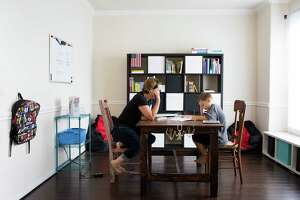 Heidi Walker sits across from her son Roanin Walker, 7, while he studies at his home classroom in Kingwood. Heidi and her husband decided to homeschool Roanin after he was denied special education. Roanin was diagnosed with attention deficit disorder, anxiety and sensory processing disorder.