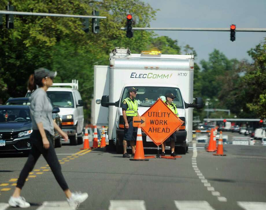 Police direct traffic around electrical utility workers at East Putnam Avenue and Mason Street in Greenwich Wednesday. More than 11,000 Greenwich residents were without power Tuesday night. Power was restored for most by midnight, however another outage affecting more than 2,000 people occurred Wednesday afternoon. Photo: Tyler Sizemore / Hearst Connecticut Media / Greenwich Time