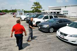 Sterling McCall Toyota internet sales manager Auggie Mathis, left, and used car manager Max Dinh walk along cars on the Val-U-Line Thursday July 26, 2018 in Houston. The Group 1 Auto dealership posted record sales, driven in part by strong used car sales. (Michael Ciaglo / Houston Chronicle)