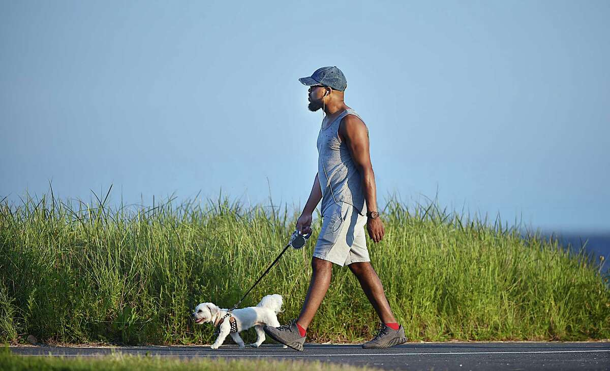 A man walks his dog at the walking path at Savin Rock Wednesday, September 5, 2018 in West Haven.