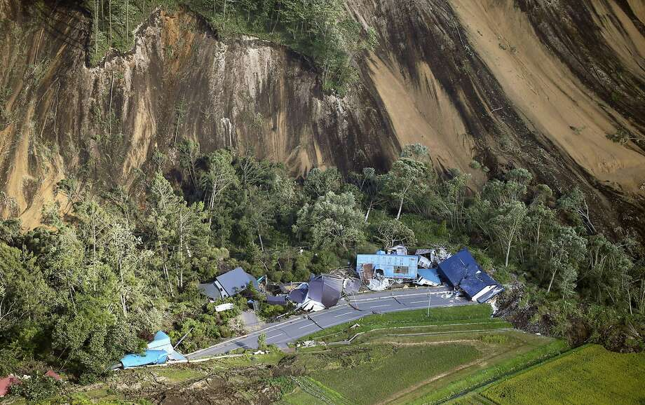 This aerial photo shows houses destroyed by a landslide after an earthquake in Atsuma town, Hokkaido, northern Japan, Thursday, Sept. 6, 2018. A powerful earthquake rocked Japan's northernmost main island of Hokkaido early Thursday, triggering landslides that crushed homes, knocking out power across the island, and forcing a nuclear power plant to switch to a backup generator. (Kyodo News via AP) Photo: Associated Press