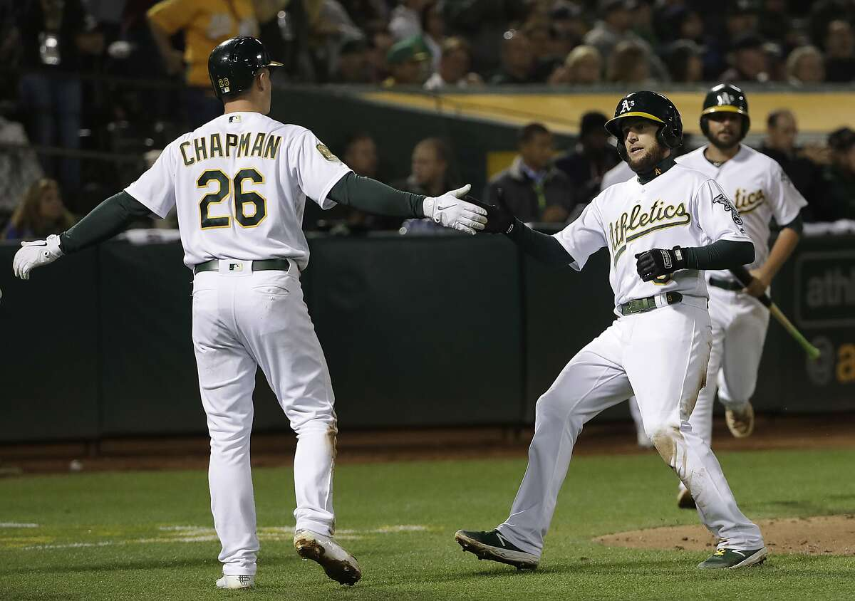 Oakland Athletics' Matt Chapman (26) celebrates with Jed Lowrie after both scored on Stephen Piscotty's single during the third inning of a baseball game against the New York Yankees in Oakland, Calif., Wednesday, Sept. 5, 2018. (AP Photo/Jeff Chiu)