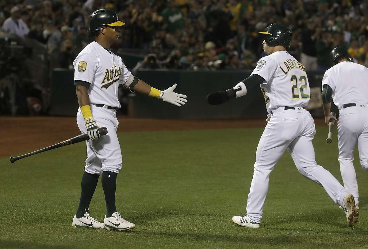 Oakland Athletics' Ramon Laureano, right, is congratulated by Khris Davis after scoring against the New York Yankees during the first inning of a baseball game in Oakland, Calif., Wednesday, Sept. 5, 2018. (AP Photo/Jeff Chiu)