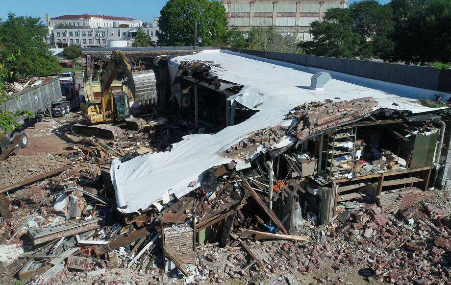Demolition crews topple the former Night's Uniform building in downtown Beaumont on Wednesday. After 93 years in operation, the company closed in 2013 and the building is now being razed to repurpose the materials according to the building's owner. Photo taken Wednesday, 9/5/18 Photo: Guiseppe Barranco/The Enterprise