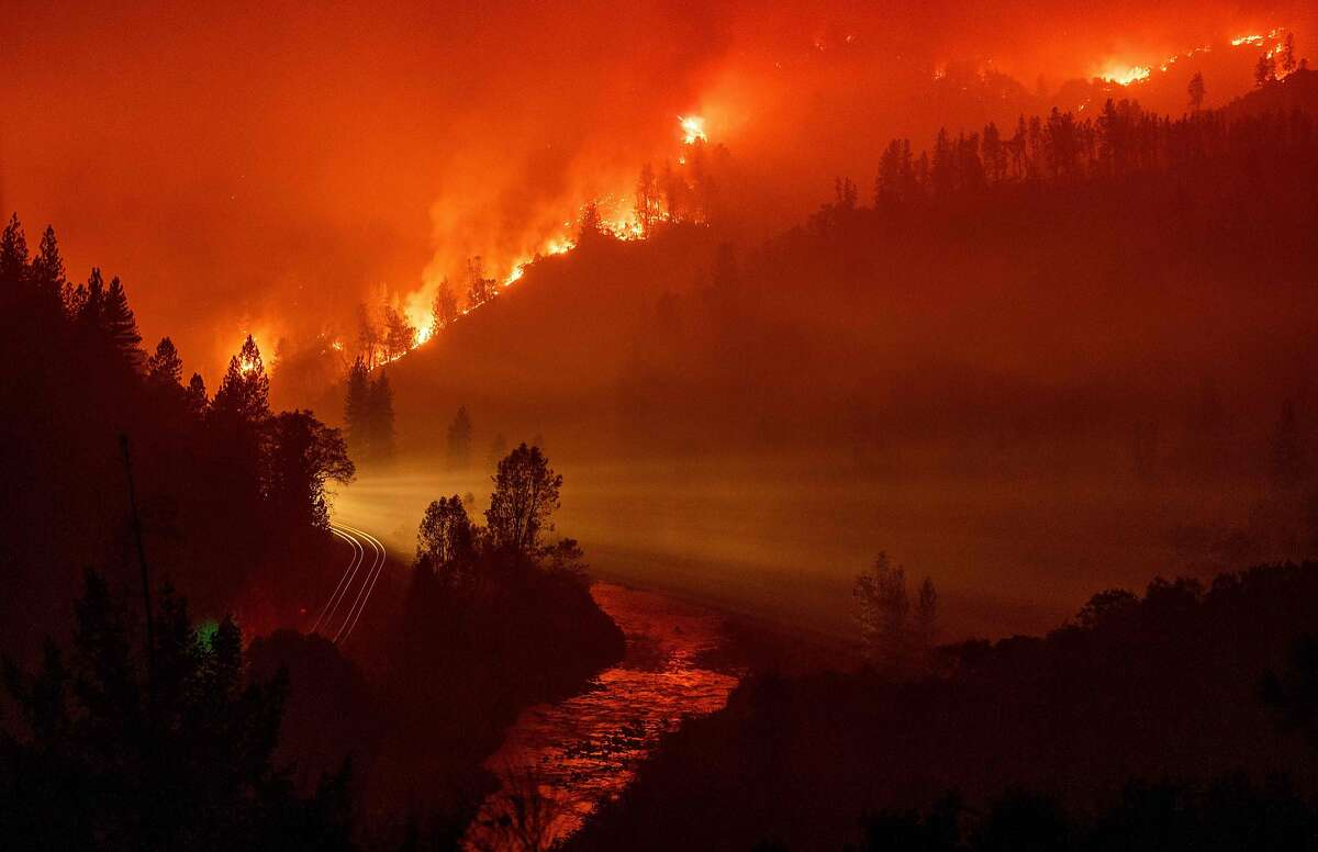 TOPSHOT - Light from a train is seen as it rounds a bend near the Sacramento River as flames from the Delta Fire fill a valley in Delta, California on September 6, 2018. (Photo by JOSH EDELSON / AFP)JOSH EDELSON/AFP/Getty Images
