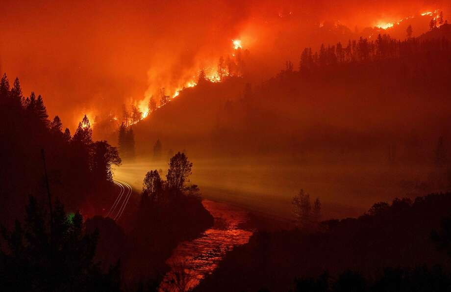 Light from a train is seen as it rounds a bend near the Sacramento River as flames from the Delta Fire fill a valley in Delta, California on September 6, 2018. Photo: Josh Edelson / AFP / Getty Images