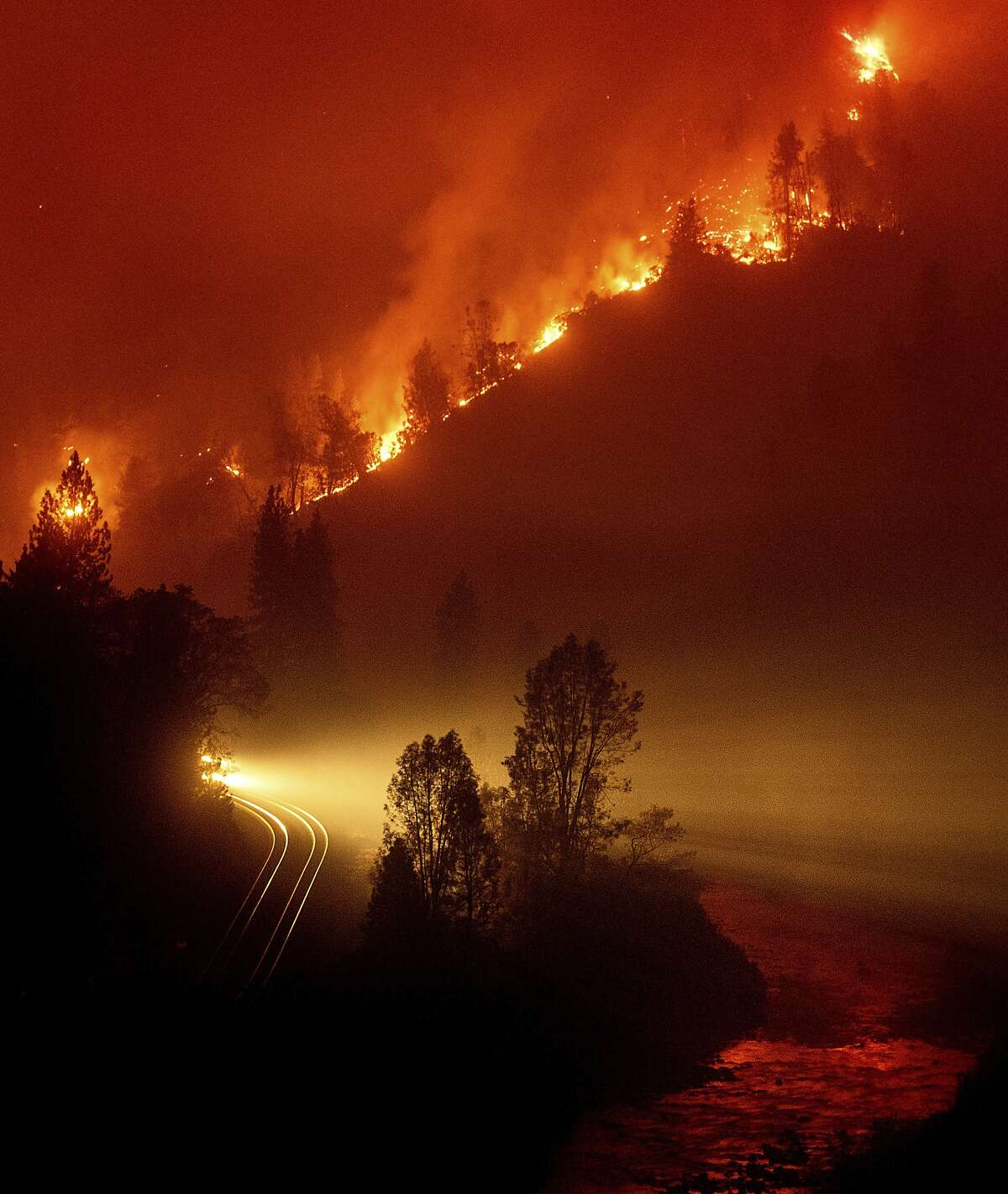 The Delta Fire burns in the Shasta-Trinity National Forest, Calif., on Thursday, Sept. 6, 2018. The wildfire closed both directions of Interstate 5 leaving trucks parked on the shoulder for more than two miles waiting to pass through. (AP Photo/Noah Berger)