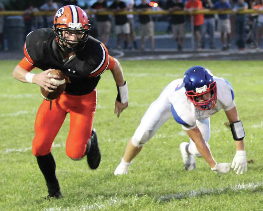 Gillespie quarterback Joey Carter (left) looks for running room after shaking a Carlinville tackler during last week's South Central Conference football game in Gillespie. The Cavaliers won 49-14 and take a No. 4 ranking in the Class 3A state poll against Litchfield on Friday night. Photo: Greg Shashack / The Telegraph
