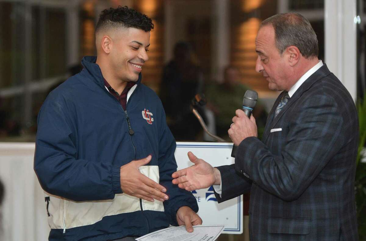 Miguel Colon (left) shakes hands in November 2016 with former Connecticut state Rep. Larry Cafero Jr., after completing the Greater Norwalk Chamber of Commerce's annual Small Business Development Academy in Norwalk, Conn.