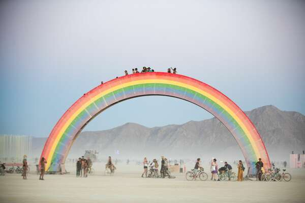"Participants attend Burning Man 2018, the largest outdoor arts festival in North America, in the Black Rock Desert of Gerlach, Nev. Pictured is the ""Rainbow Bridge"" by artist Josh Zubkoff. (""Sidney Erthal works with the Burning Man Project as an archivist, photographer, and translator."")"