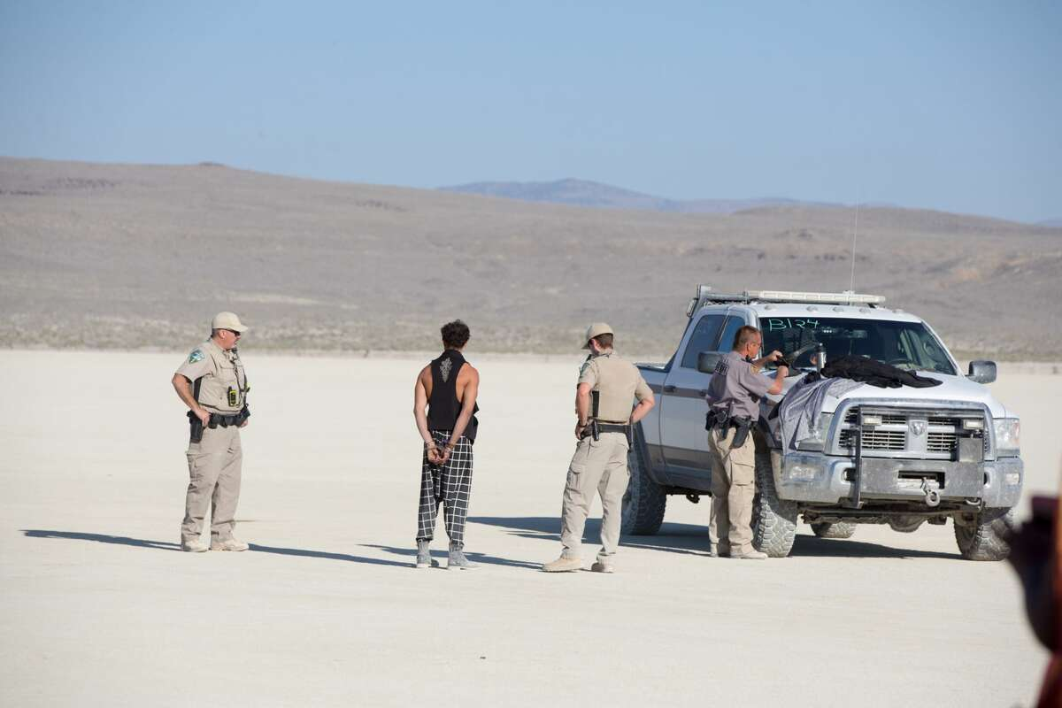 A participants at Burning Man 2018 is handcuffed by authorities in the Black Rock Desert of Gerlach, Nev.