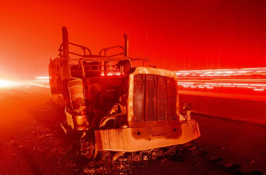 A fire vehicle passes by an abandoned burned out truck along interstate 5 after the Delta Fire tore through the region and jumped the road in Delta, California on September 5, 2018. Photo: JOSH EDELSON/AFP/Getty Images / This content is subject to copyright.