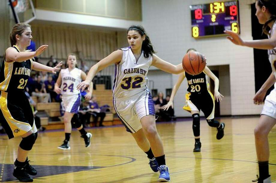 Calvary Baptist's Tamrah Konieczka, right, prepares to drive past Faith Baptist of Davison's Kurstin Hine during a 2016 game at the CBA gym. (Daily News file photo) / Midland Daily News