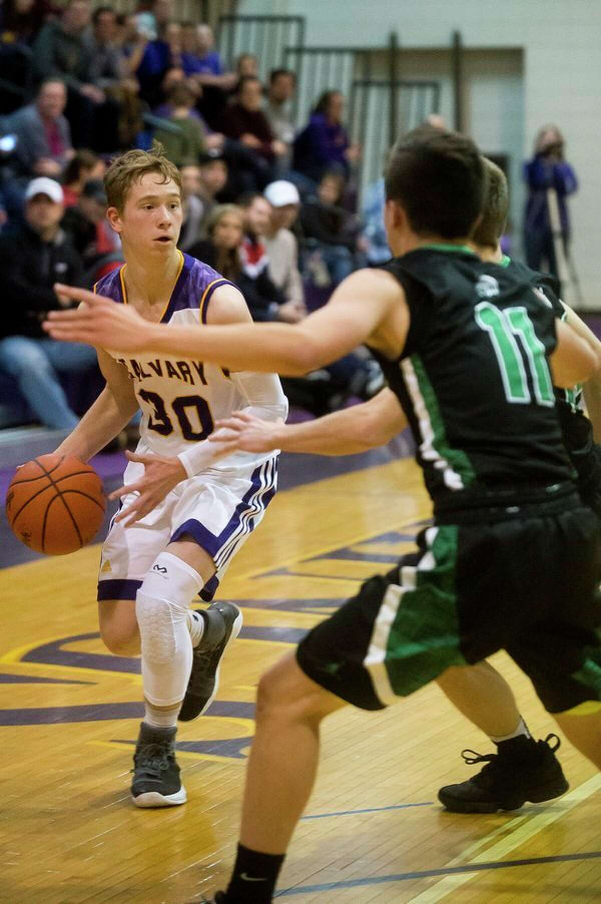 Calvary Baptist's Mark Dickerson dribbles down the court duringa game against Houghton Lake at CBA this past January. (Daily News file photo)