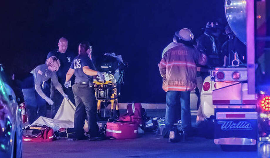 Paramedics and firefighters work at the scene of a fatal crash where two Alton men were killed late Wednesday. Photo: Nathan Woodside/Hearst Illinois