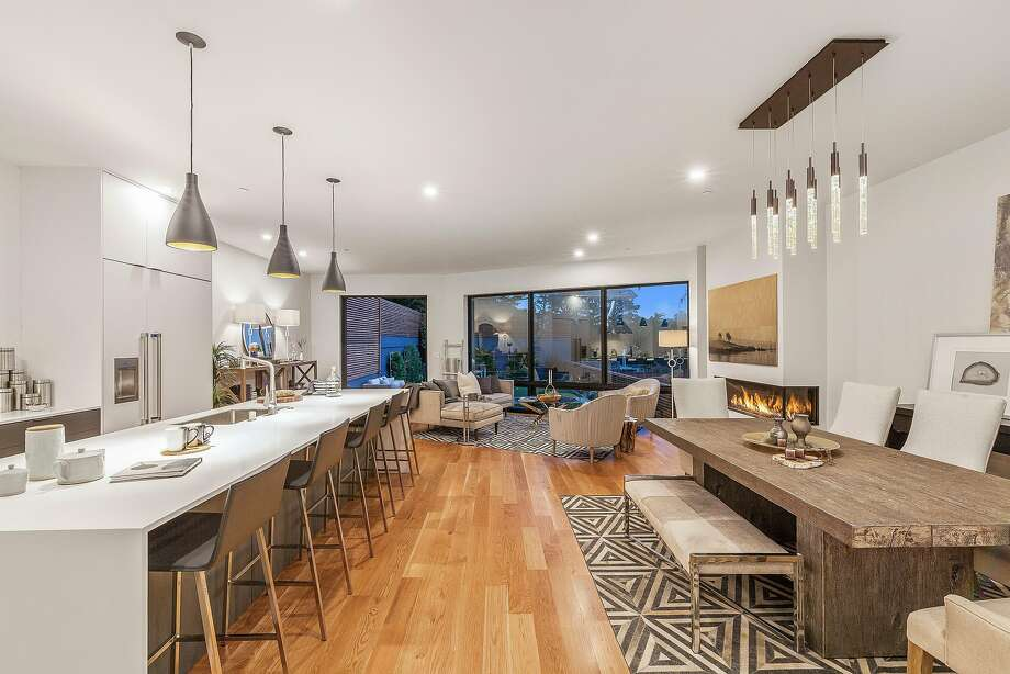 The great room at 844 Duncan St. in Noe Valley features hardwood flooring, a gas fireplace and a kitchen island with waterfall edges. Photo: Open Homes Photography