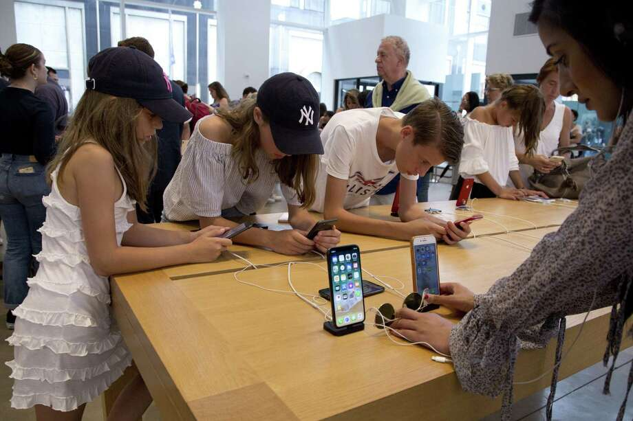 In this Aug. 2, 2018, file photo customers browse in an Apple store in New York. Stamford-based Charter Communications has rolled out its Spectrum Mobile platform, which is compatible with smartphones including iPhones. Photo: Mark Lennihan / Associated Press / Copyright 2018 The Associated Press. All rights reserved.