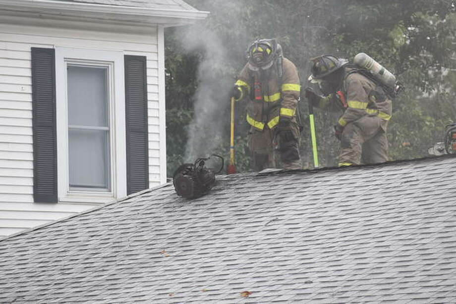Firefighters vent the roof of an East College Avenue garage during a fire Thursday. Photo: Nick Draper | Journal-Courier
