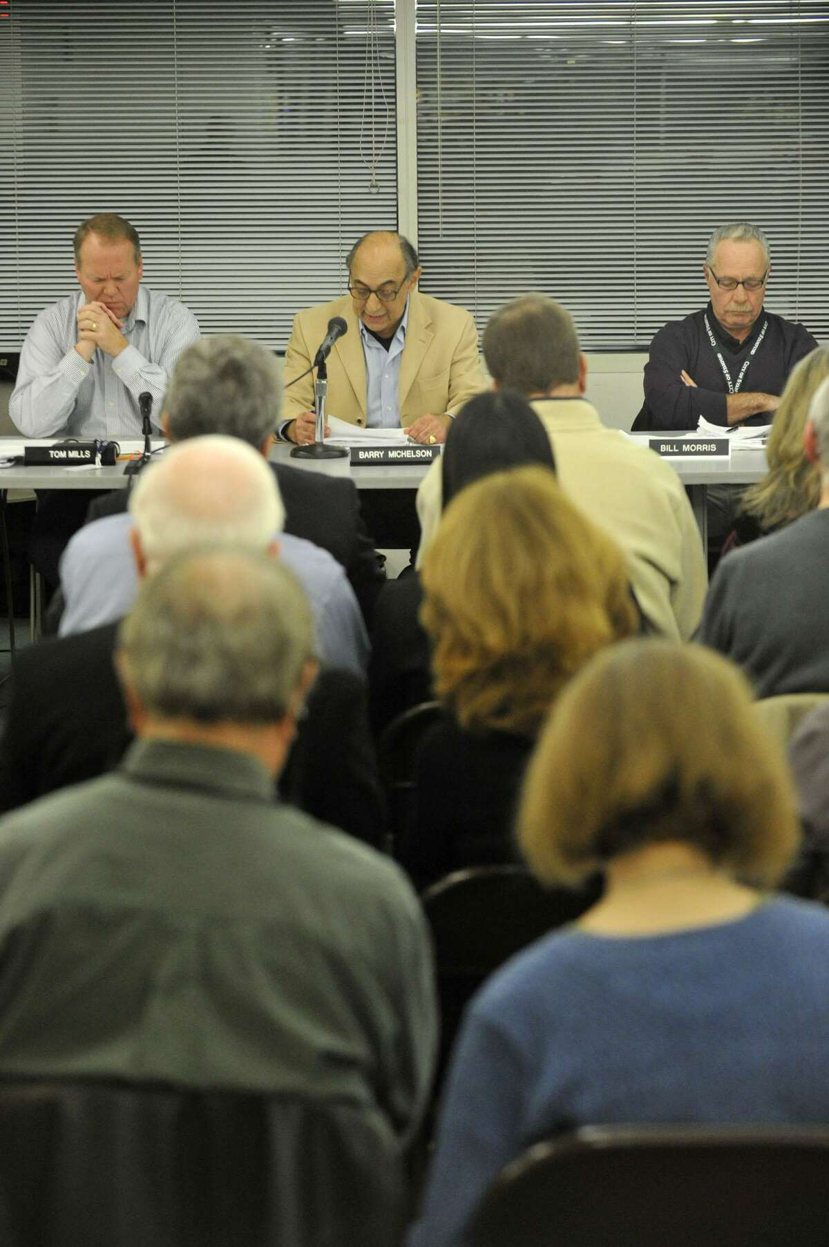 Zoning Board member Barry Michelson, top center, speaks as Chairman Tom Mills, left, and fellow board member Bill Morris, listen during the public hearing on the proposed redevelopment of the Stamford train station parking garage at the Stamford Government Center in November 2014.