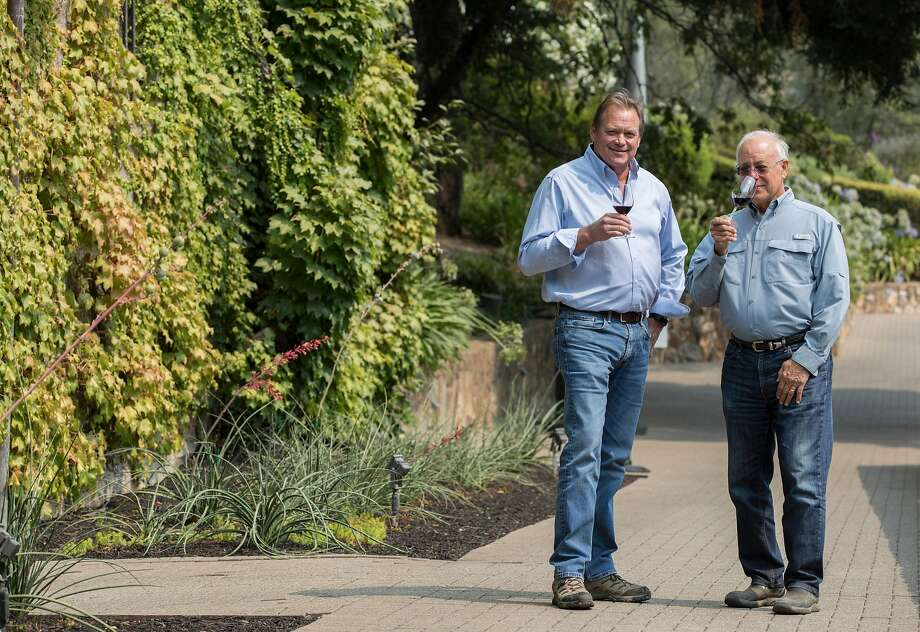 Winemakers Dave Guffy (left) and Randle Johnson sip by the ivy wall of the Hess art gallery, housed in a building from 1903. Photo: Jessica Christian / The Chronicle