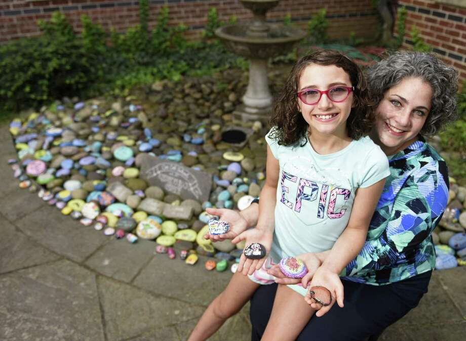 "Fourth-grader Ava Perez and her mother, Elisha Perez, pose at the Kindness Rocks Garden at Cos Cob School in the Cos Cob section of Greenwich, Conn. Thursday, Sept. 6, 2018. Ava began making ""kindness rocks"" for students with messages of positivity as an icebreaker when she transferred to Cos Cob School. Now there is a dedicated garden for the rocks at Cos Cob School for students to take a rock and leave a rock. Photo: Tyler Sizemore / Hearst Connecticut Media / Greenwich Time"