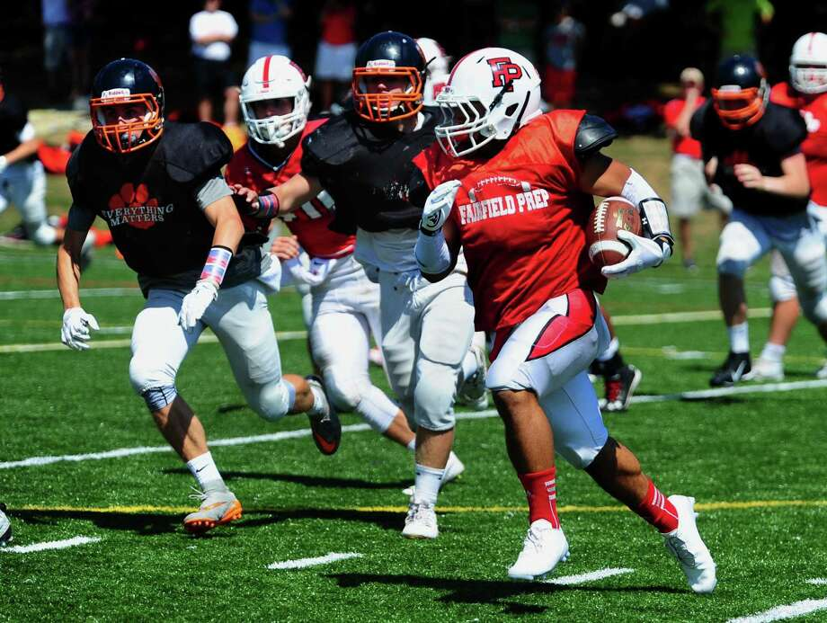 Fairfield Prep's Doug Harrison carries the ball during a scrimmage against Ridgefield before the start of the 2016 season. Photo: Christian Abraham / Hearst Connecticut Media / Connecticut Post