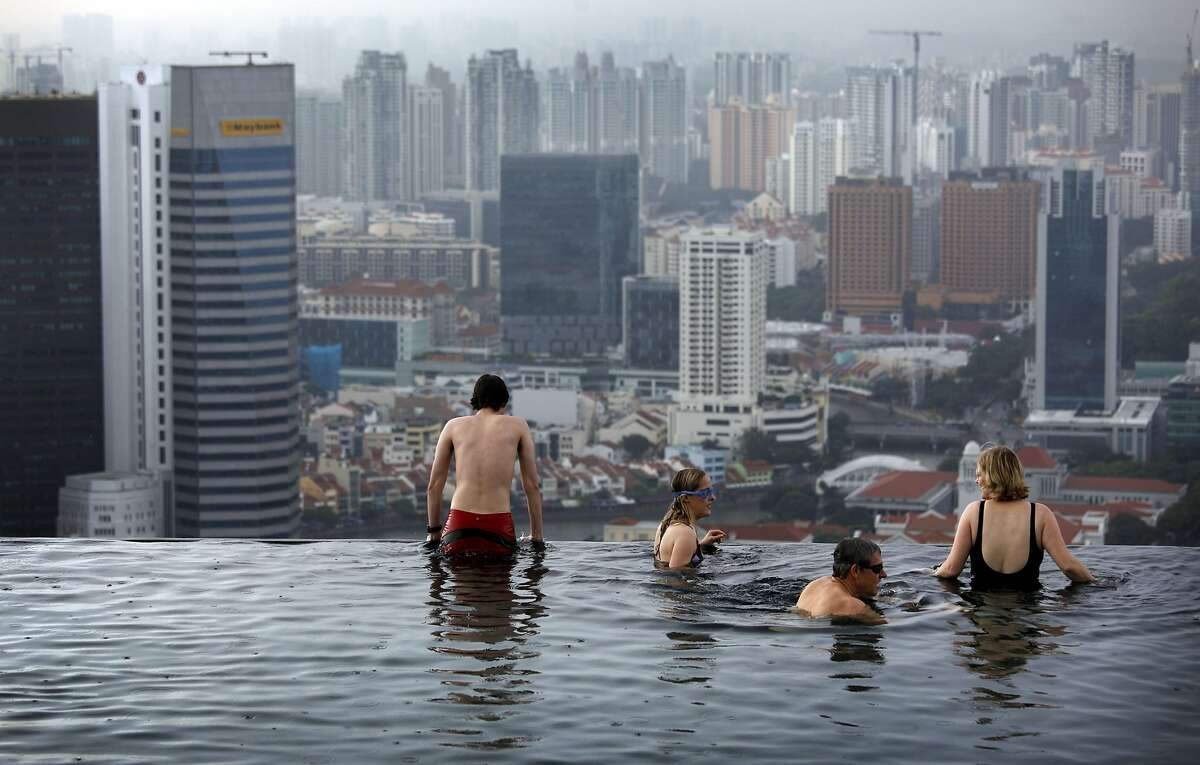 Tourists relax in an infinity pool on the roof of the Marina Bay Sands Hotel tower on Monday Jan. 3, 2011 in Singapore.