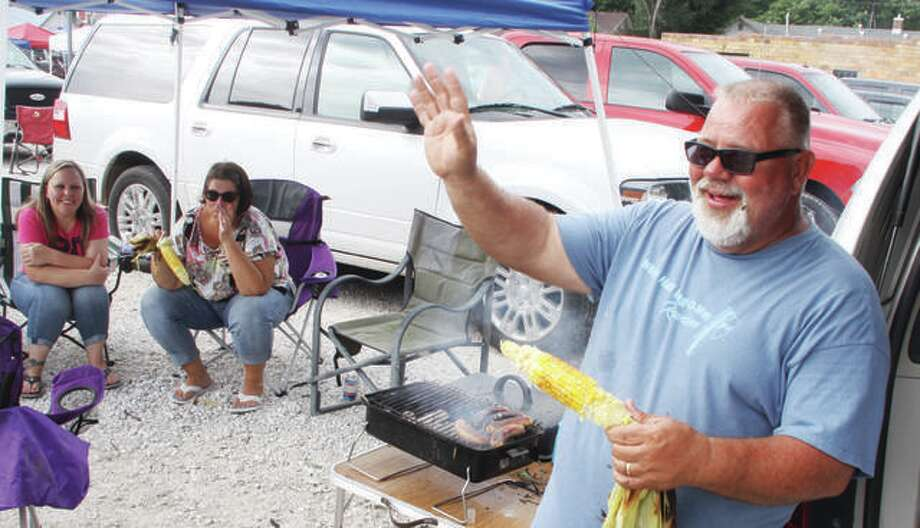 "Bob Eden, of Delhi, waves to friends while eating grilled sweet corn while waiting for the Eldred American Legion's ""Queen of Hearts"" raffle last month. Some changes in a proposed ordinance regulating the popular and sometimes controversial raffles are expected in Godfrey, after the document was given a first reading at Wednesday's Village Board meeting. Photo: Scott Cousins 