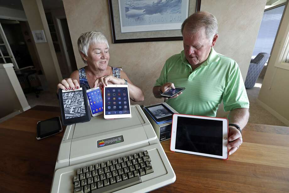 Kathy and Steve Dennis display several of their own cell phones and tablets along with their 1980s-era Apple II+ computer bought for their then-young sons. Photo: Elaine Thompson / Associated Press