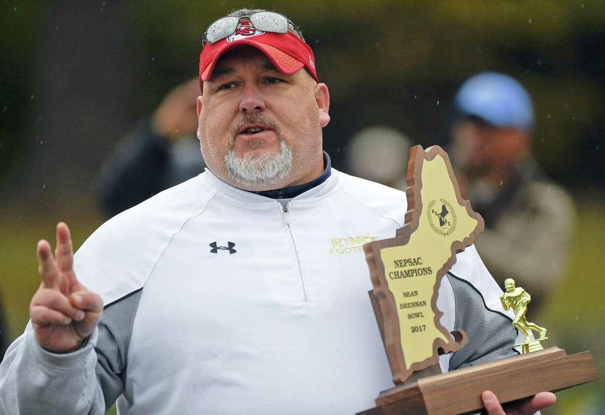 King coach Dan Gouin holds the championship trophy following the Sean Brennan Bowl of the NEPSAC Class C football championship on Nov. 18.