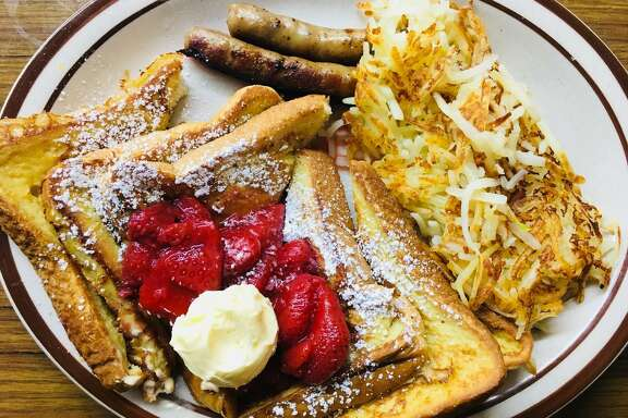 Diners can order French toast topped with strawberries with a side of hash browns and sausage at Huffman Cafe.