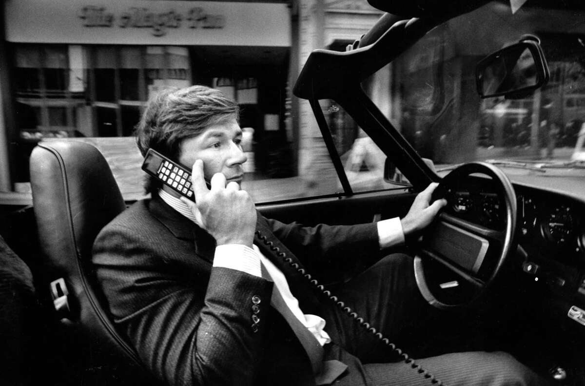 Investment banker Michael Yancey uses his cellular phone in a Porsche. Sept. 28, 1987.