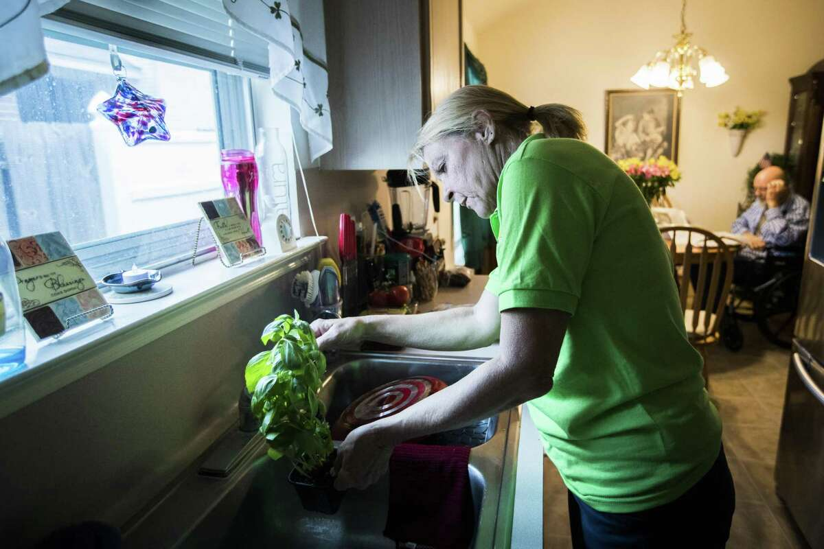Glenda Roewe, 61, a caregiver with FirstLight waters a basil plant for her clients during a home visit to Kenath Fether, 78, in Tomball, Thursday, Aug. 16, 2018. After several strokes Fether, a Vietnam veteran and his wife feel more comfortable when a caregiver accompanies him while his wife runs errands.
