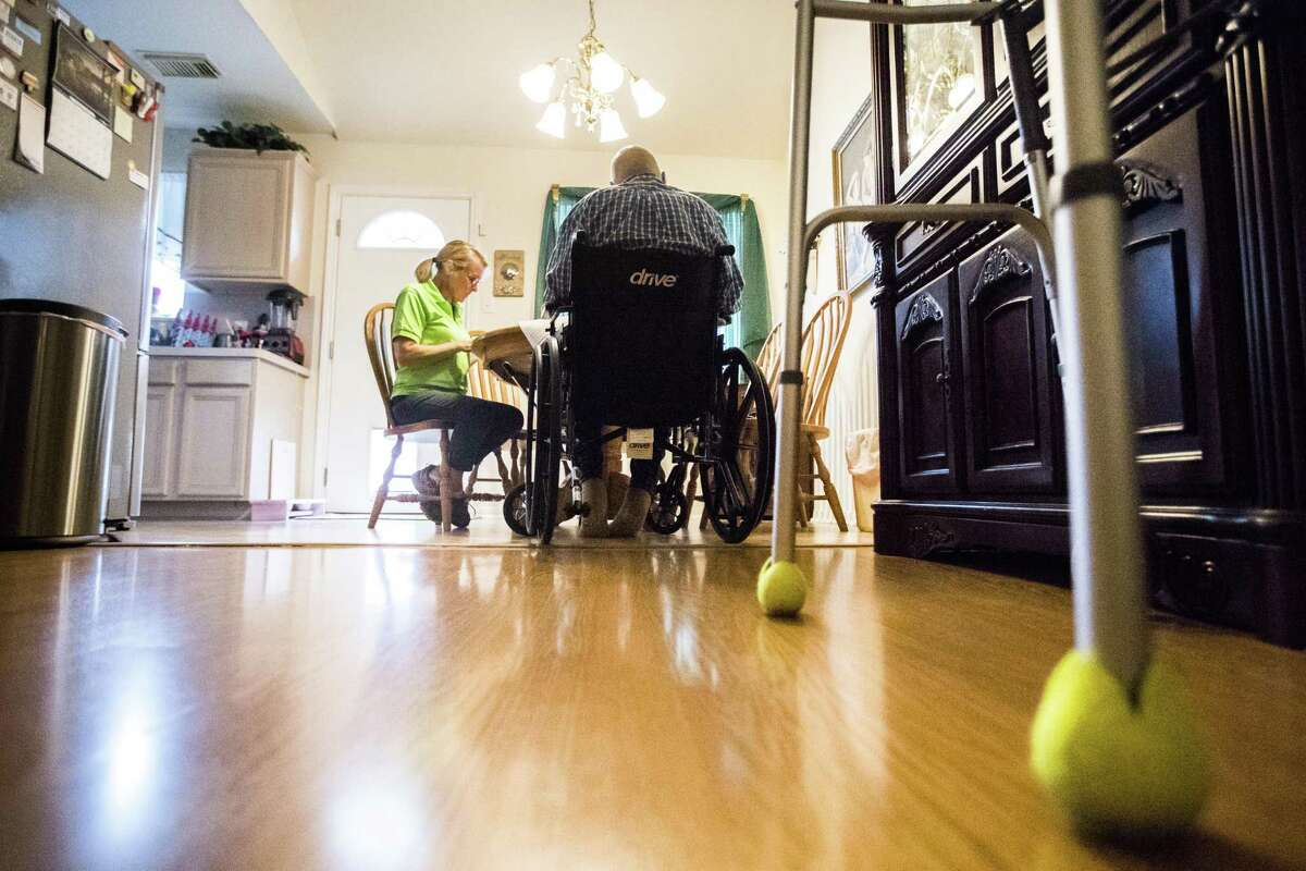 Glenda Roewe, 61, goes over paperwork accompanying her client Kenath Fether, 78, who no longer feels comfortable spending time alone while his wife runs errands. Roewe is a home caregiver employed by FirstLight. Thursday, Aug. 16, 2018, in Houston.