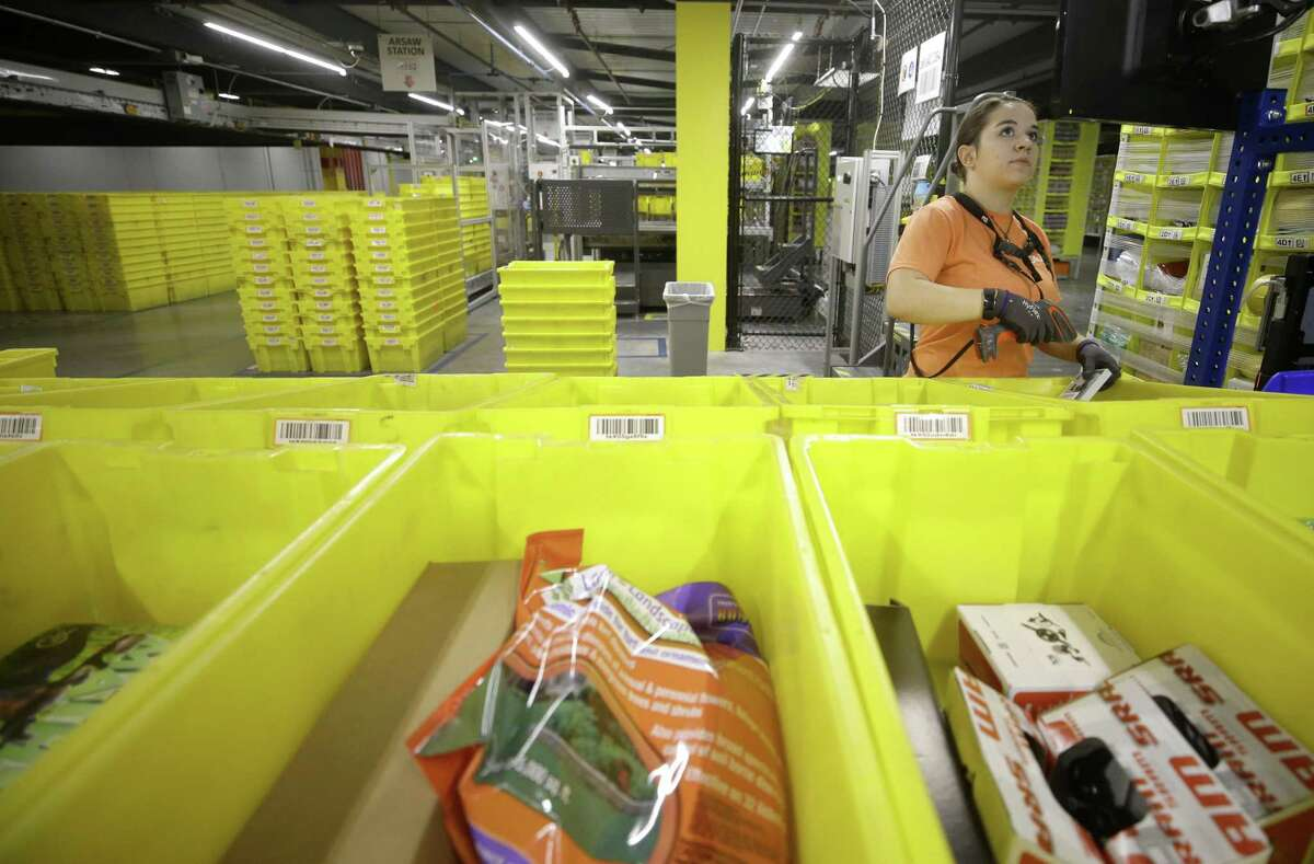 Jessi Henson works at a stowing station where she puts items into inventory at the Amazon HOU2 Fulfillment Center, 10550 Ella Blvd., Thursday, Sept. 6, 2018, in Houston.