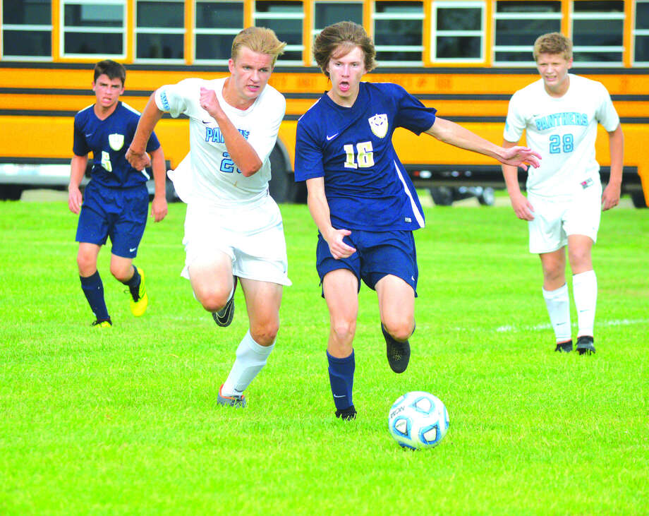 Father McGivney junior Keller Weir, right, chases down the ball while being pursued by Jerseyville junior Sam Bartels during the first half of Thursday's game at Father McGivney. Photo: Scott Marion